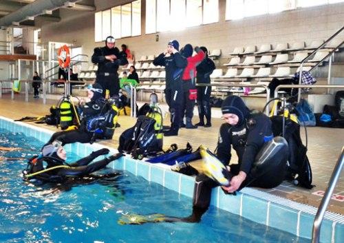 Últimos preparativos de Fernando antes de entrar al agua con el traje seco. Gonzalo le aguarda en el agua.