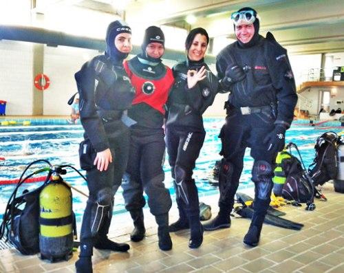 Marta, Mapi, Zoe y Carlos equipados con sus trajes secos antes de iniciar sus practicas subacuáticas.