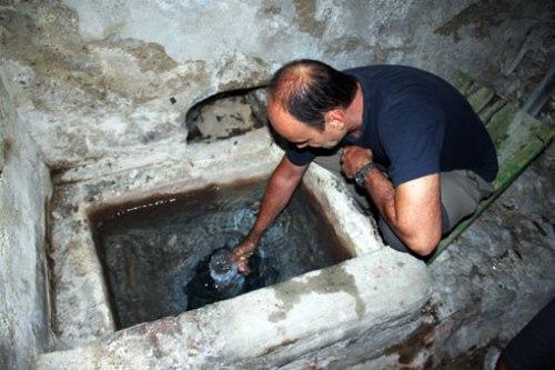 """Alfonso Pardo recoge una muestra de agua de la surgencia de la""""Fuente de la Belleza"""" (Fotografía: Tomás Arruebo)."""